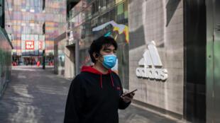 Un homme portant un masque passe devant un magasin Adidas à Pékin le 19 mars 2020
