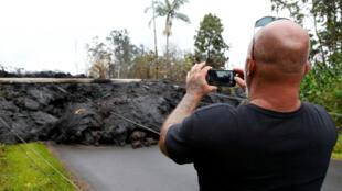 Un turista fotografía una masa de lava fría que causó la caída de un poste de electricidad en la zona residencial de Leilani Estates. Mayo 9 de 2018.