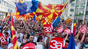 """La gente agita banderas macedonias y europeas mientras asisten a una manifestación de campaña por el """"sí"""" antes de un referéndum sobre si cambiar el nombre del país a """"República del Norte de Macedonia"""", en Skopje el 16 de septiembre de 2018."""