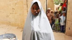 """تسلقت حسنة محمد البالغة 13 عاما سياجا للهرب من هجوم مشتبه به لجماعة """"بوكو حرام"""" الجهادية على مدرسة في دابشي بشمال شرق نيجيريا في 22 فبراير 2018"""
