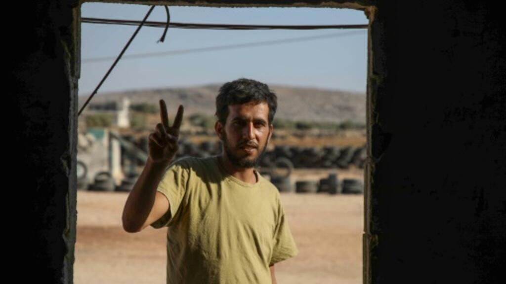 Mohammad al-Naeemi, a Syrian who returned from exile in Germany to join a rebel group, flashes a victory sign at a training camp near the Bab al-Hawa crossing between Iblib province and Turkey on July 18, 2019