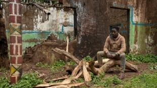 Teketel Memhiru sits by the ruins of his house, burned down during ethnic clashes at Cherqo village