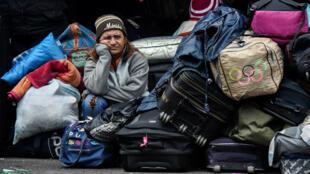 Una mujer venezolana espera afuera de la oficina de migración de Colombia a lo largo del puente internacional Rumichaca antes de cruzar de Ipiales en Colombia, a Tulcán en Ecuador, el 20 de agosto de 2018.