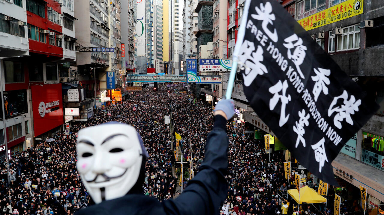 Un manifestante con una máscara de Guy Fawkes ondea una bandera durante una marcha del Día de los Derechos Humanos, organizada por el Frente Civil de Derechos Humanos, en Hong Kong , China, el 8 de diciembre de 2019.