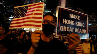 A man holds the US flag and a placard as anti-government demonstrators march in protest against the invocation of the emergency laws in Hong Kong on October 14, 2019.