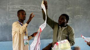 Los trabajadores ad hoc del INEC cuentan las papeletas electorales en la escuela primaria Giginyu en el estado de Kano, Nigeria, el 23 de febrero de 2019.