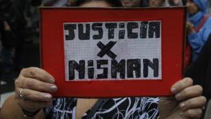 Una mujer sostiene la bandera justicia por Nisman en la Plaza de Mayo durante la Marcha del Silencio en Buenos Aires.