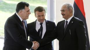 Le président français, Emmanuel Macron, entouré de Fayez al-Sarraj (à g.) et Khalifa Haftar, le 25 juillet 2017 à la Celle-Saint-Cloud.