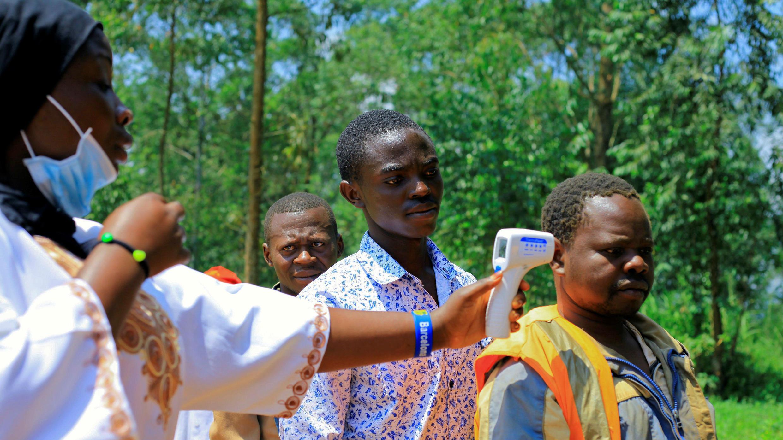 Un trabajador de salud congoleño revisa la temperatura de un hombre antes del lanzamiento de una campaña de vacunación contra el mortal virus del Ébola cerca de la aldea de Mangina, cerca de la ciudad de Beni en la provincia de Kivu del Norte, 8 de agosto de 2018.