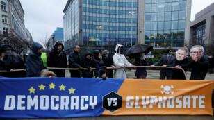 Tras el anuncio, un grupo de personas protestó en Bélgica con máscaras en representación de los rostros del presidente de la Comisión Europea, Jean Claude Juncker, y del comisario europeo de Salud, Vytenis Andriukaitis.