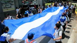 Un grupo de manifestantes sostiene una gran bandera nacional durante una protesta contra el Gobierno del presidente Daniel Ortega en Managua, Nicaragua, el 18 de junio de 2019.