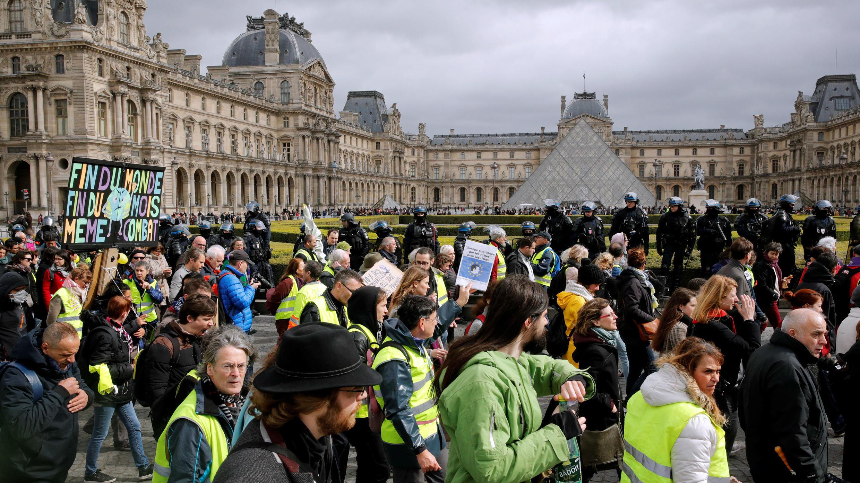 Manifestantes con chalecos amarillos pasan frente al emblemático Museo del Louvre durante la jornada número 17 de las manifestaciones contra el Gobierno. París, Francia, marzo 9 de 2019.