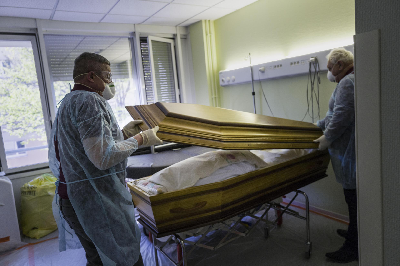 Des employés d'une entreprise funéraire ferment le cercueil d'une personne décédée du Covid-19 dans un hôpital à Mulhouse, le 5 avril 2020