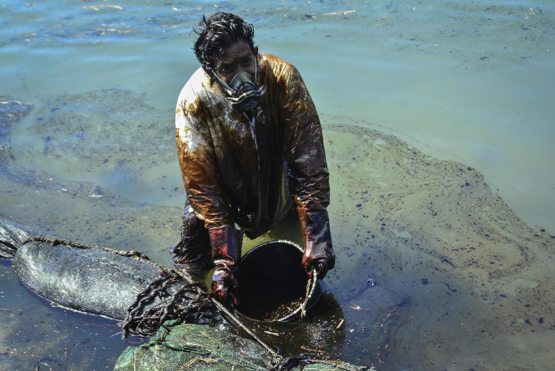 Un hombre intenta retirar petróleo derramado por el barco MV Wakashio en las aguas de isla Mauricio el 8 de agosto de 2020.