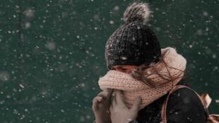 Una mujer se cubre la cara en Nueva York donde nieve y temperaturas extremas causan caos.