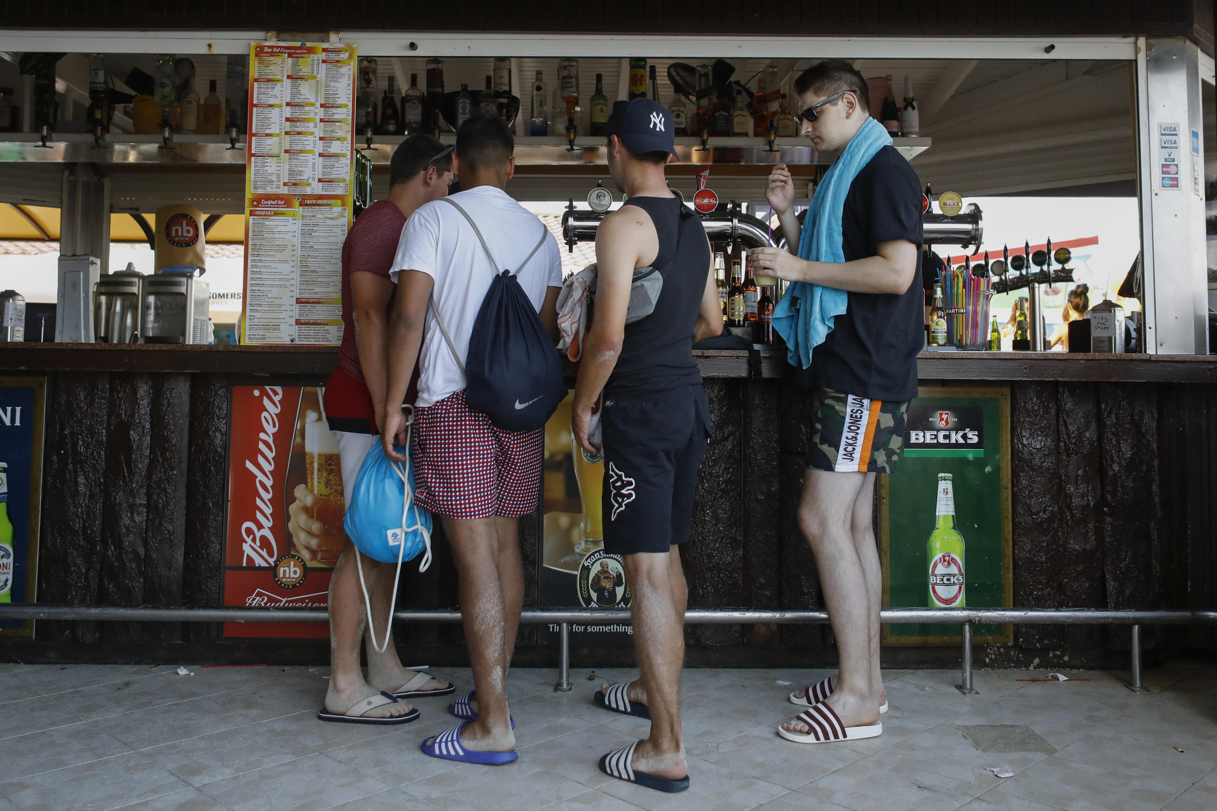 Tourists buy drinks at a bar in the Cypriot resort town of Ayia Napa on July 18, 2019.