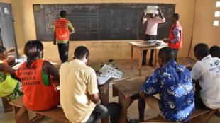 Des membres de la commission électorale comptent les bulletins de vote dans une école de Lomé, le 25 avril.