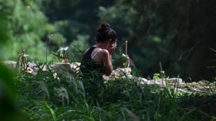 Une jeune femme pleure la mort de l'un de ses  proches, victime du coronavirus, à son enterrement au cimetière du Parque Memorial Jardin de Los Angeles (près de   Tegucigalpa), le 4 juillet 2020