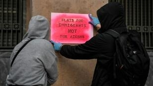 "Activists stencil a slogan reading ""Flats for immigrants not for Airbnb"" on a wall during a demonstration outside the EU offices in central Athens"