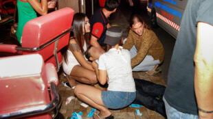 Des personnes viennent en aide à un blessé, le 11 août 2016, après une explosion dans la station balnéaire thaïlandaise de Hua Hin.