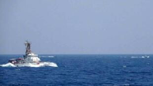 صورة وزعتها البحرية الأميركية في 10 أيار/مايو 2021، تظهر في خلفيتها قطعتان بحريتان إيرانيتان على مقربة من سفينة أميركية في مضيق هرمز.