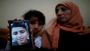 La madre de Mohammed Ayoub, el joven palestino de 14 años asesinado por las tropas israelíes durante las protestas en la frontera entre Israel y Gaza, muestra la foto de su hijo. Franja de Gaza, el 21 de abril de 2018.