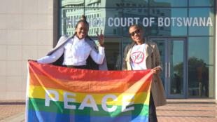 Activistas posan con una bandera del arco iris mientras celebran frente al Tribunal Superior de Botswana, en Gaborone, la despenalización de la homosexualidad,  el 11 de junio de 2019.