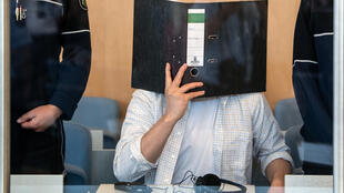 Defendant Sief Allah H. holds a folder in front of his face at the start of his trial on June 7, 2019 at a court in Duesseldorf, western Germany