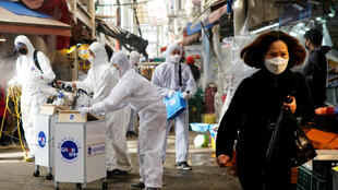A woman wearing a mask to prevent contracting the new coronavirus walks near employees from a disinfection service company sanitizing a traditional market in Seoul, South Korea on February 26, 2020.