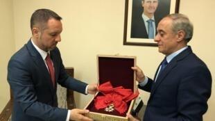 Un représentant des affaires étrangères syriennes remet la Grand'croix de la Légion d'honneur française à l'ambassade roumaine, qui fait l'intermédiaire avec les autorités françaises en Syrie.
