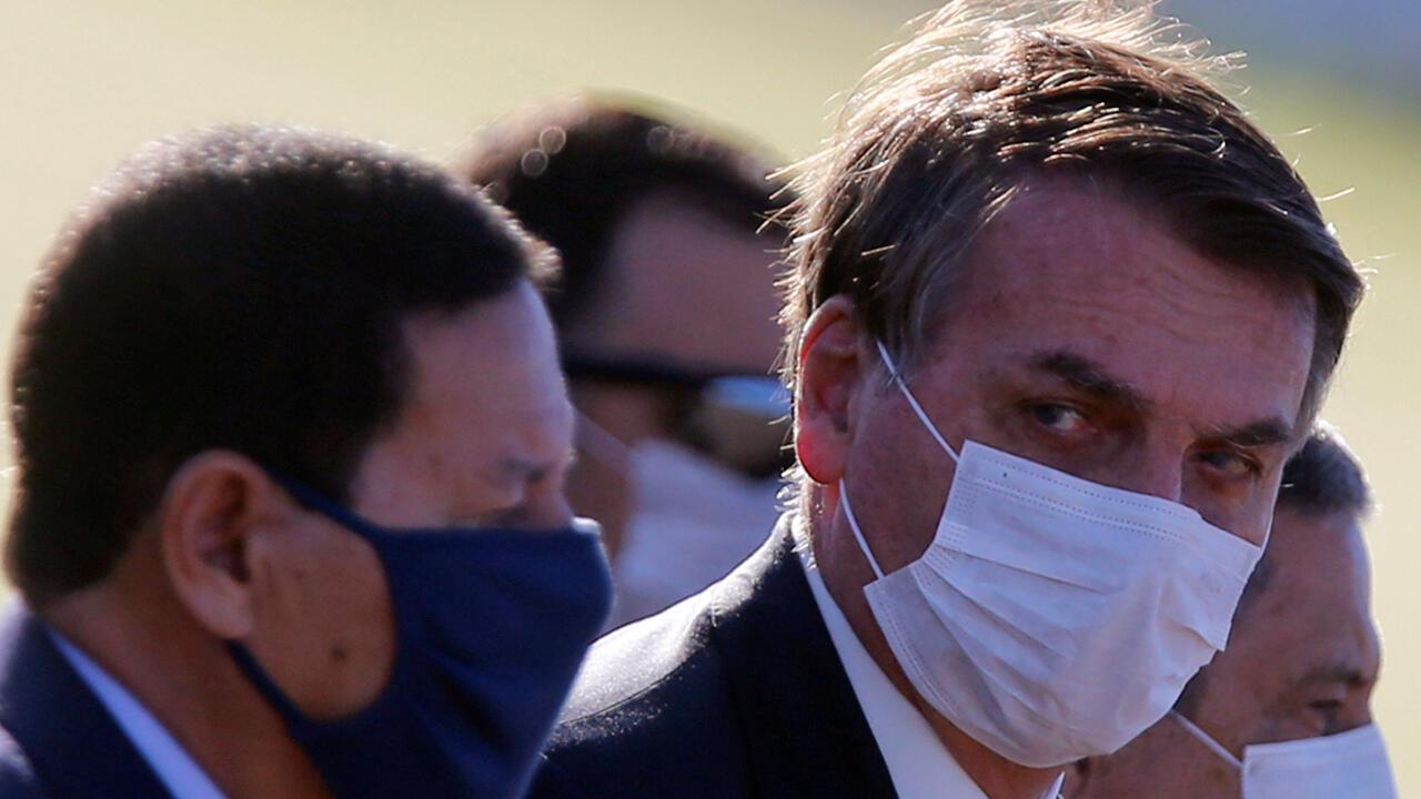 El presidente de Brasil, Jair Bolsonaro, con una máscara protectora y otros ministros de Brasil asisten a una ceremonia de izado de la bandera nacional frente al Palacio Alvorada, en medio del brote de la enfermedad por coronavirus, en Brasilia, Brasil, 12 de mayo de 2020.