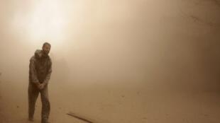 رجل يسير وسط غبار كثيف تسببت به الغارات التي نفذتها قوات النظام على دوما في الغوطة الشرقية في السابع من شباط/فبراير 2018