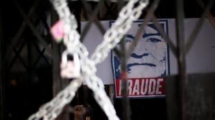 """Un póster con la plantilla del presidente de Bolivia, Evo Morales, en el que se lee """"Fraude"""" ante las instalaciones de la estatal TV y Radio Patria Nueva de Bolivia después de que los manifestantes lo cerraron durante una protesta contra el Gobierno en La Paz, Bolivia, el 9 de noviembre de 2019."""