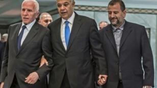 رئيس المخابرات المصرية خالد فوزي بين عضو اللجنة المركزية لحركة فتح عزام الأحمد (يسار) ونائب رئيس حركة حماس صالح العاروري خلال توقيع اتفاق المصالحة بين فتح وحماس في القاهرة 12 تشرين الأول/أكتوبر 2017