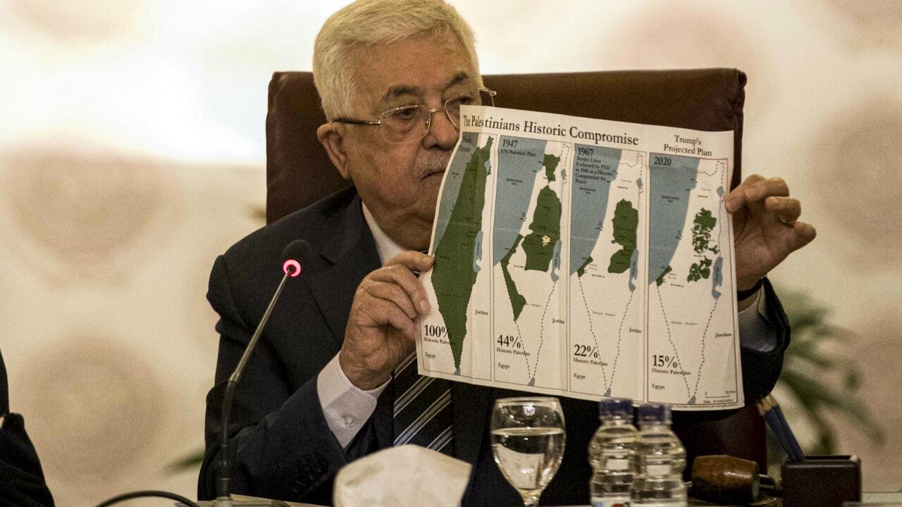 El presidente palestino Mahmud Abbas sostiene un cartel que muestra mapas de la Palestina histórica (de izquierda a derecha), el plan de partición de las Naciones Unidas de 1947 en Palestina, las fronteras de 1948-1967 entre los territorios palestinos e Israel, y un mapa actual de los territorios palestinos sin Israel, en El Cairo, Egipto, el 1 de febrero de 2020.