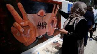 امرأة ترسم غرافيتي على الحائط في يوم السجين الفلسطيني 17 أبريل/نيسان 2016