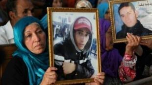 أفراد من عائلات ضحايا الثورة التونسية ضد نظام الرئيس زين العابدين بن علي يحملون في 13 يوليو/تموز 2018 صور أشخاص قتلوا خلال عهد بن علي
