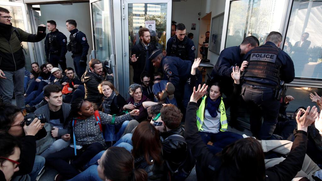 """Activistas ambientales bloquean la entrada del Ministerio de Ecología, Energía y Desarrollo Sostenible durante una """"acción de desobediencia civil"""" para instar a los líderes mundiales a actuar contra el cambio climático, en La Defense, cerca de París, Francia."""