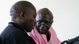 L'ancien politicien rwandais Léon Mugesera (à droite) parle à son avocat, dans le tribunal à Kigali, le 15 avril.