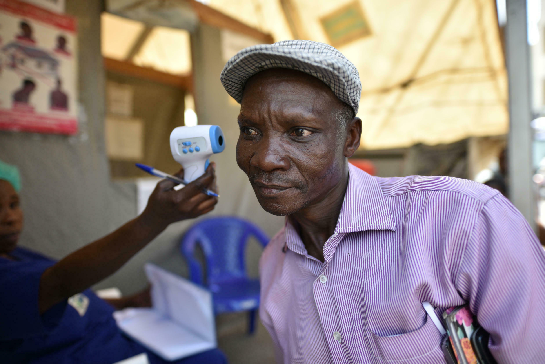 Un trabajador de la salud verifica la temperatura corporal de un hombre como parte de la prueba de ébola al ingresar al Hospital General de Goma, República Democrática del Congo, el 15 de julio de 2019.