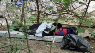 Expulsé du camp de La Chapelle, un migrant clandestin dort dans un parc du XVIIIe arrondissement, à Paris.