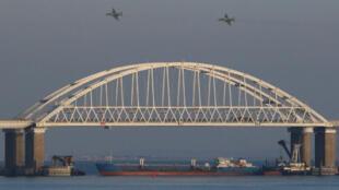 Aviones de combate rusos vuelan sobre un puente que conecta a Rusia con la península anexada de Crimea, después de que tres buques de la armada ucraniana fueron detenidos por Rusia, al presuntamente ingresar al Mar de Azov a través del Estrecho de Kerch, el 25 de noviembre de 2018.