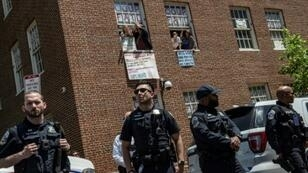 Pro-Nicolas Maduro supporters and activists occupying the Venezuelan embassy in Washington waved earlier this week from a window to Reverend Jesse Jackson (unseen) who came to support them. The opposition said Thursday the building had been cleared by police