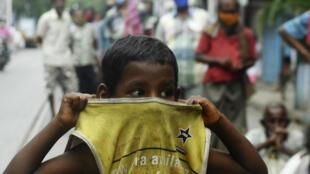 Un niño cubre su boca mientras espera en una cola para recoger comida gratis al lado de una carretera durante el confinamiento por el coronabirus anunciado por el gobierno, el 25 de julio de 2020 en Calcuta