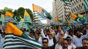Los manifestantes pakistaníes portan banderas de Cachemira administrada por Pakistán durante una protesta anti-india en Karachi, Pakistán, el 18 de agosto de 2019.