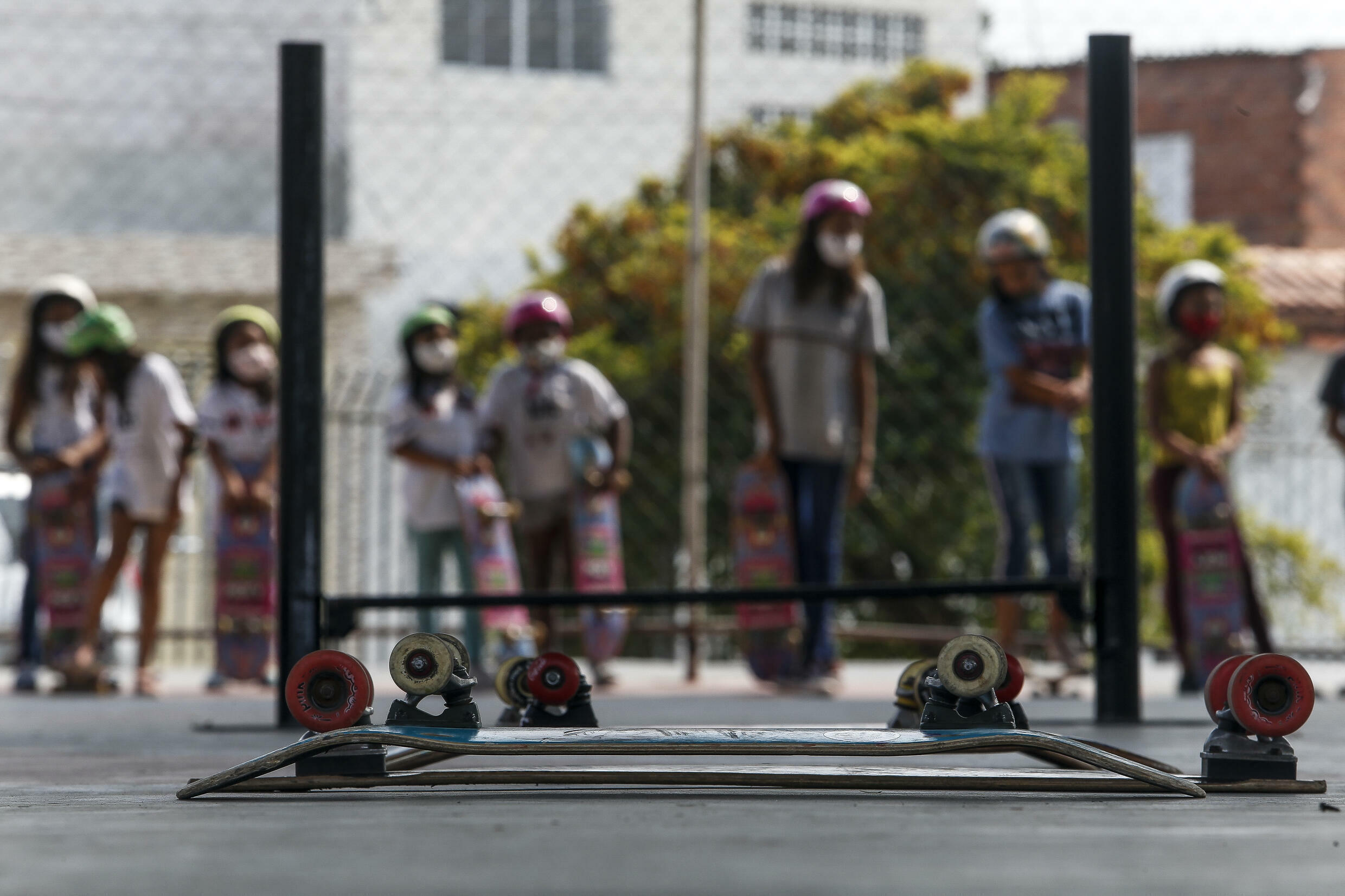 Young girls in Poa, a suburb of Sao Paulo, get ready to take their turn skateboarding