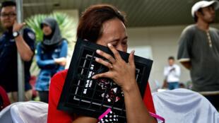 Des proches de passagers du vol de la compagnie aérienne  AirAsia, à l'aéroport de Surabaya (île de Java), le 29 décembre 2014.