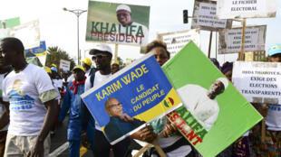 Des manifestants arborant des photos de Karim Wade et de Khalifa Sall, à Dakar, le 29 novembre 2018.