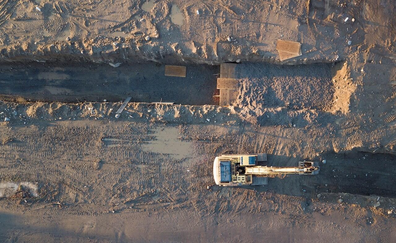 En una fotografía aérea se ve una retroexcavadora junto a grandes trincheras funerarias y edificios abandonados en Hart Island, ubicada en Long Island, frente a la costa del Bronx, Nueva York, EE. UU., El 10 de abril de 2020.