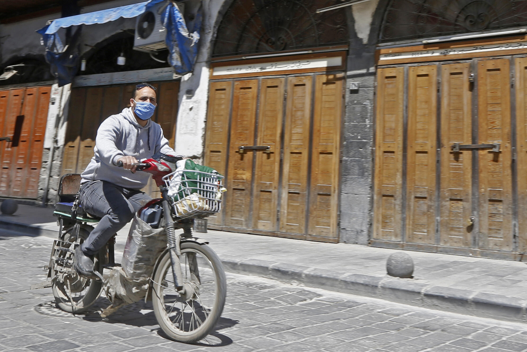 A Syrian man, wearing a protective face mask to protect against the coronavirus (COVID-19) pandemic, rides his motorcycle down a street near the Old City of the capital Damascus on April 14, 2020.